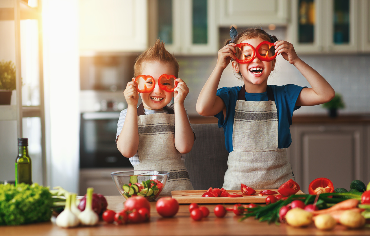 Alimentação saudável. Crianças felizes prepara salada de legumes na cozinha